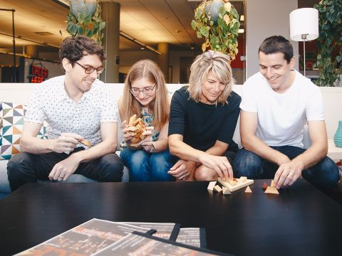 Four Toast employees relax on a couch in the office.